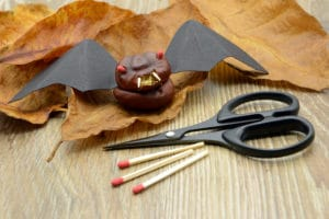 tinker small Halloween bat figure made of chestnut and paper. scissors and fire match aside.