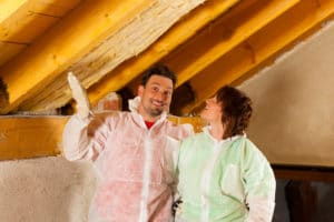 Couple in attic with protective jumpers.